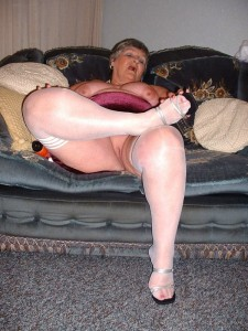 Sexy grandma in a red velvet skirt with white stockings