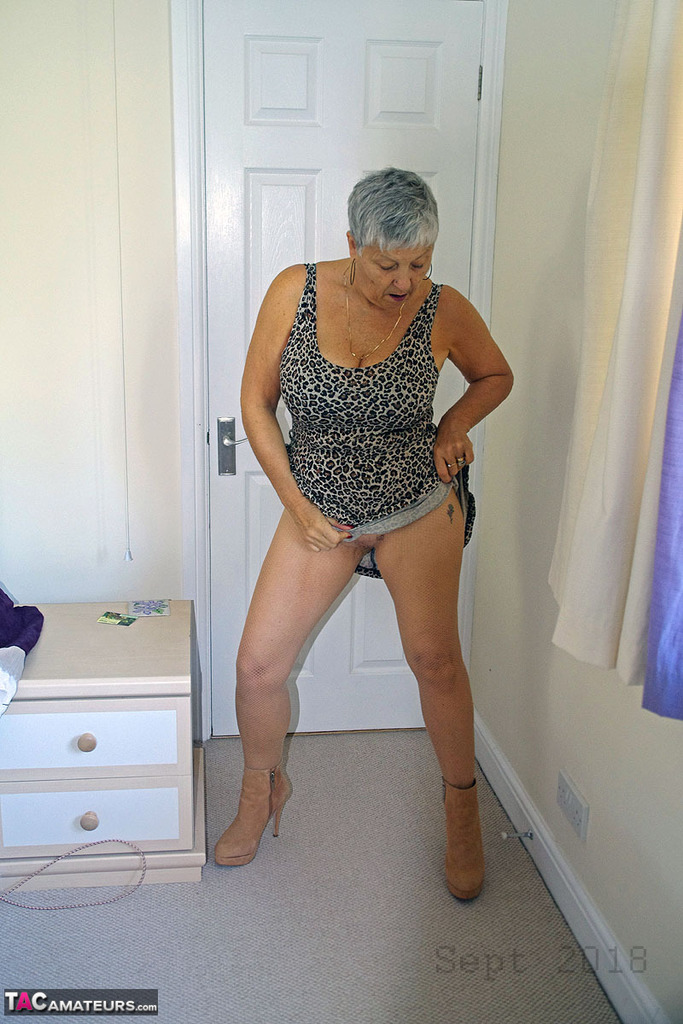 Sexy Gilf opens her legs and shows off her pussy through see through tights